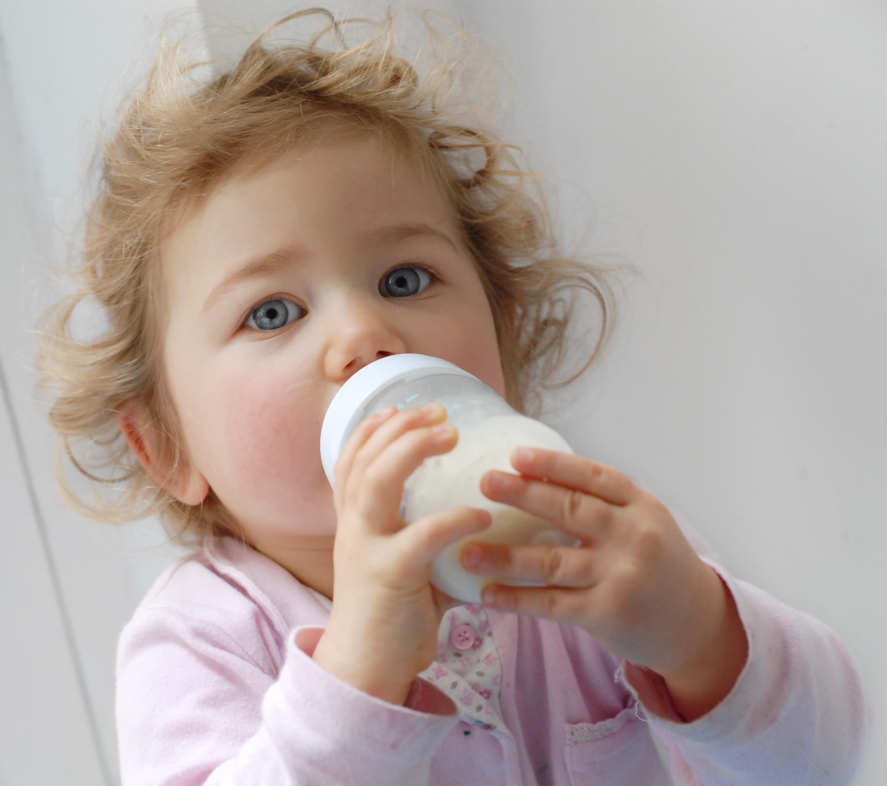 enfant qui boit un biberon de lait de croissance