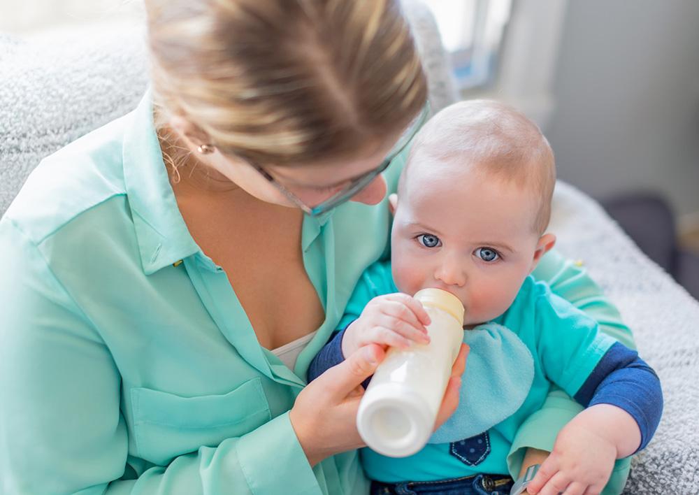 auxiliaire de puériculture donnant un biberon à un bébé