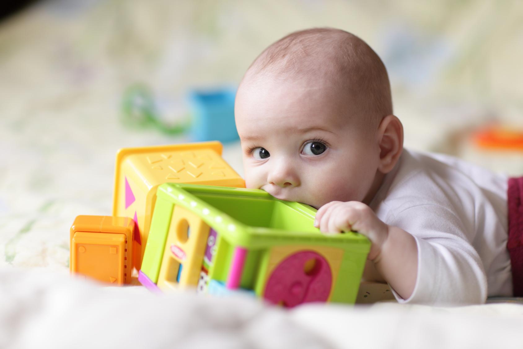 bébé qui met un jouet dans sa bouche