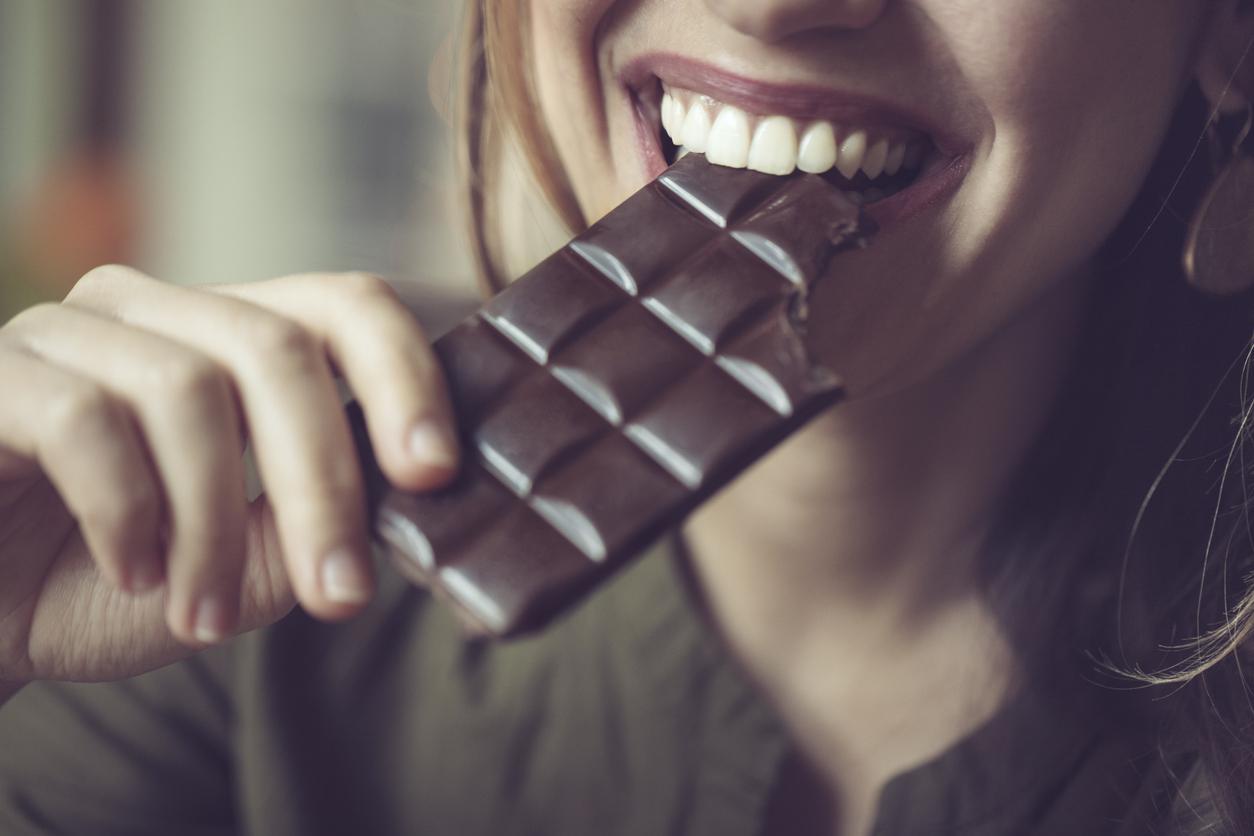 femme qui croque dans une tablette de chocolat