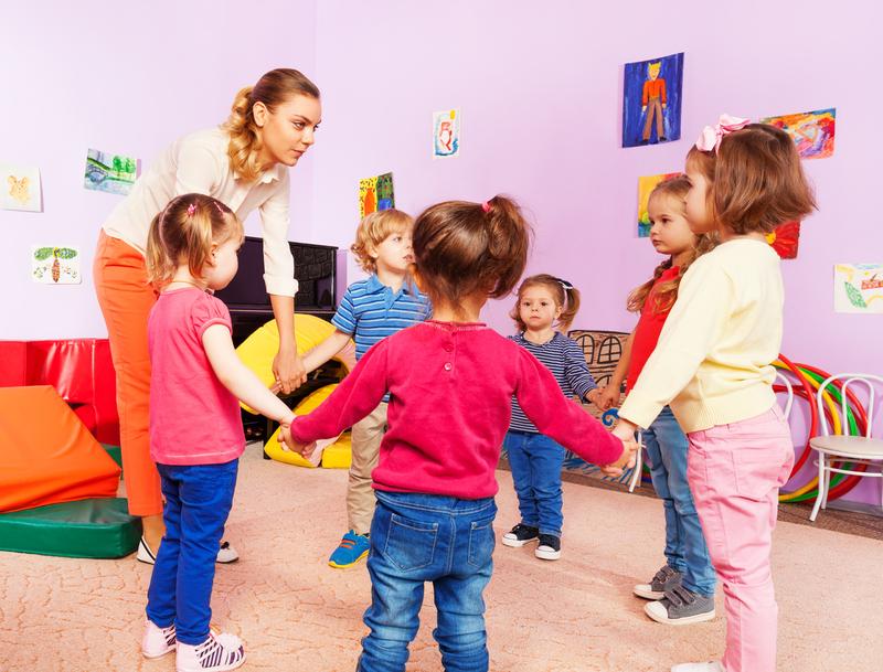 Des enfants font la ronde avec leur atsem à l