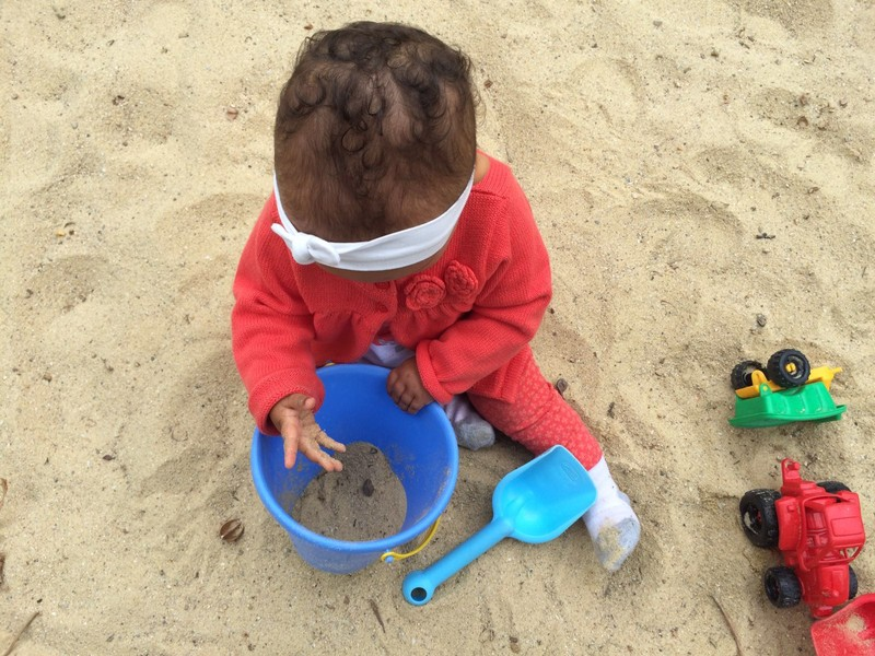 petite fille  les mains dans le sable