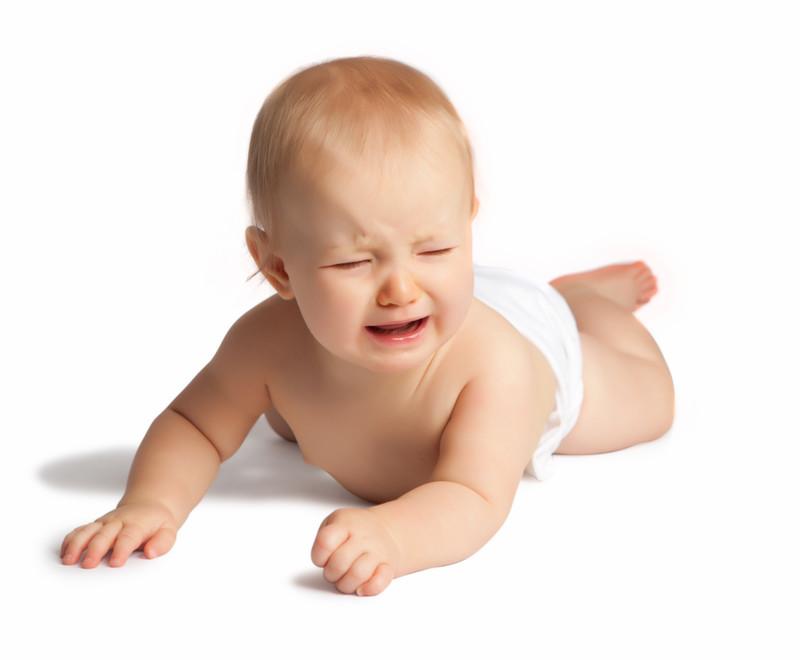 Un bébé en couche pleure.