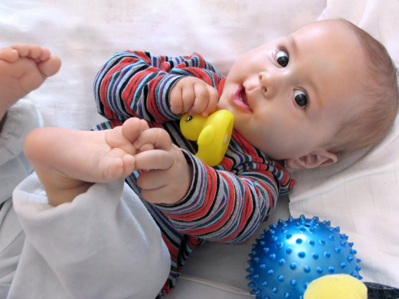 Un bébé joue avec ses pieds et un canard