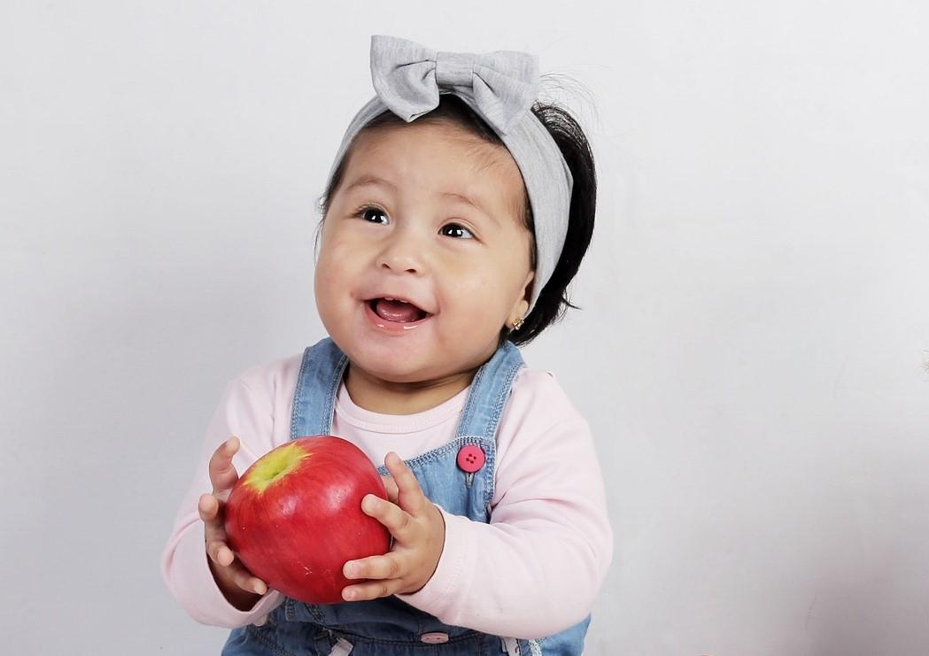 petite fille qui mange une pomme