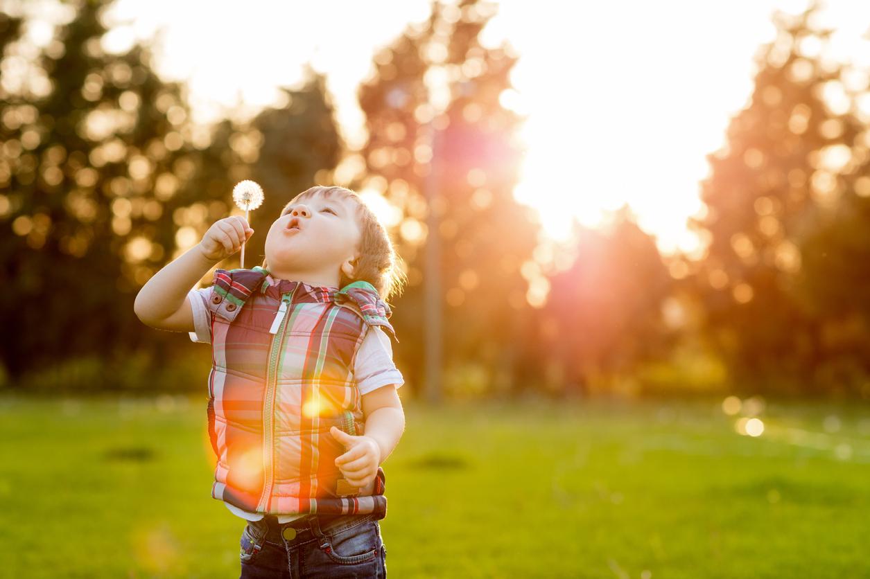 petit garçon qui souffle dans une fleur