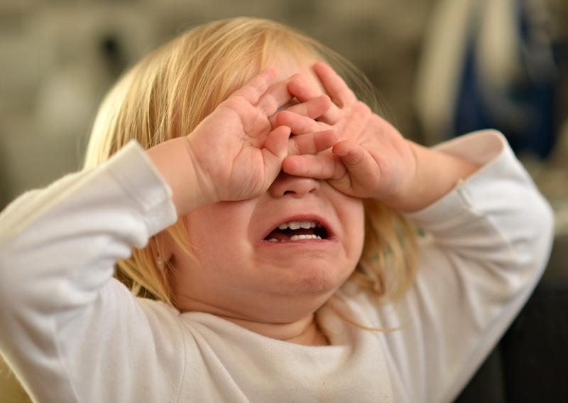 enfant en pleurs se cache les yeux