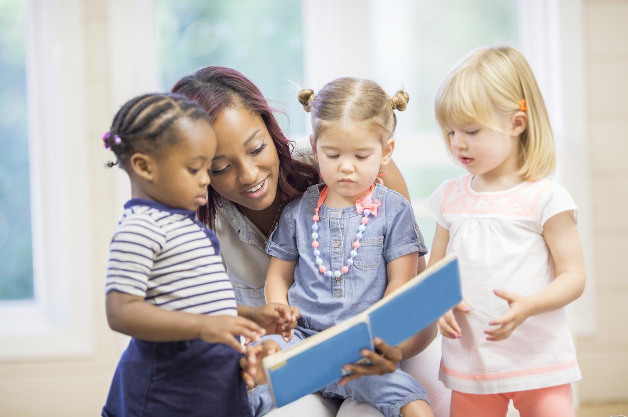 Enfants avec professionnelle lisant un livre