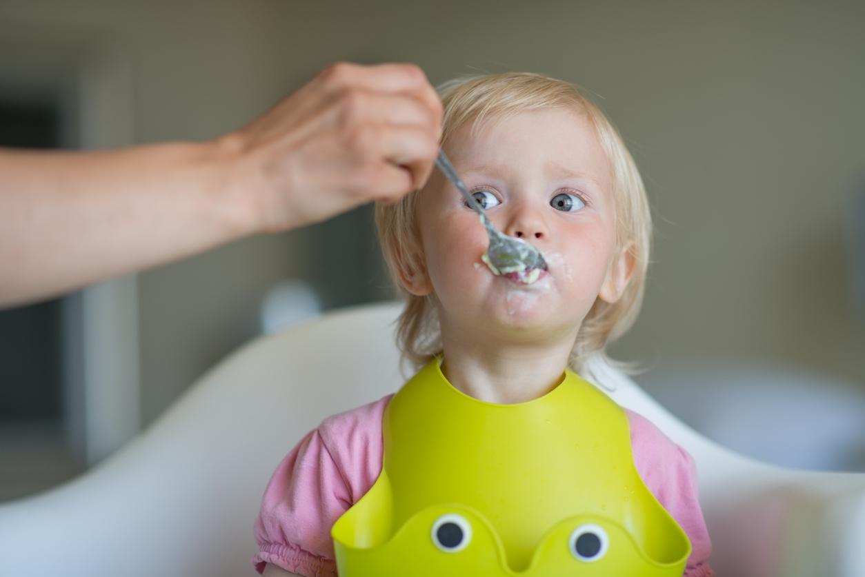 adute donne à manger à un enfant en EAJE