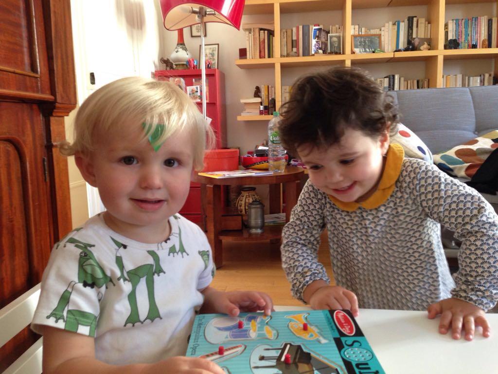 deux enfants jouent avec puzzle et gommettes