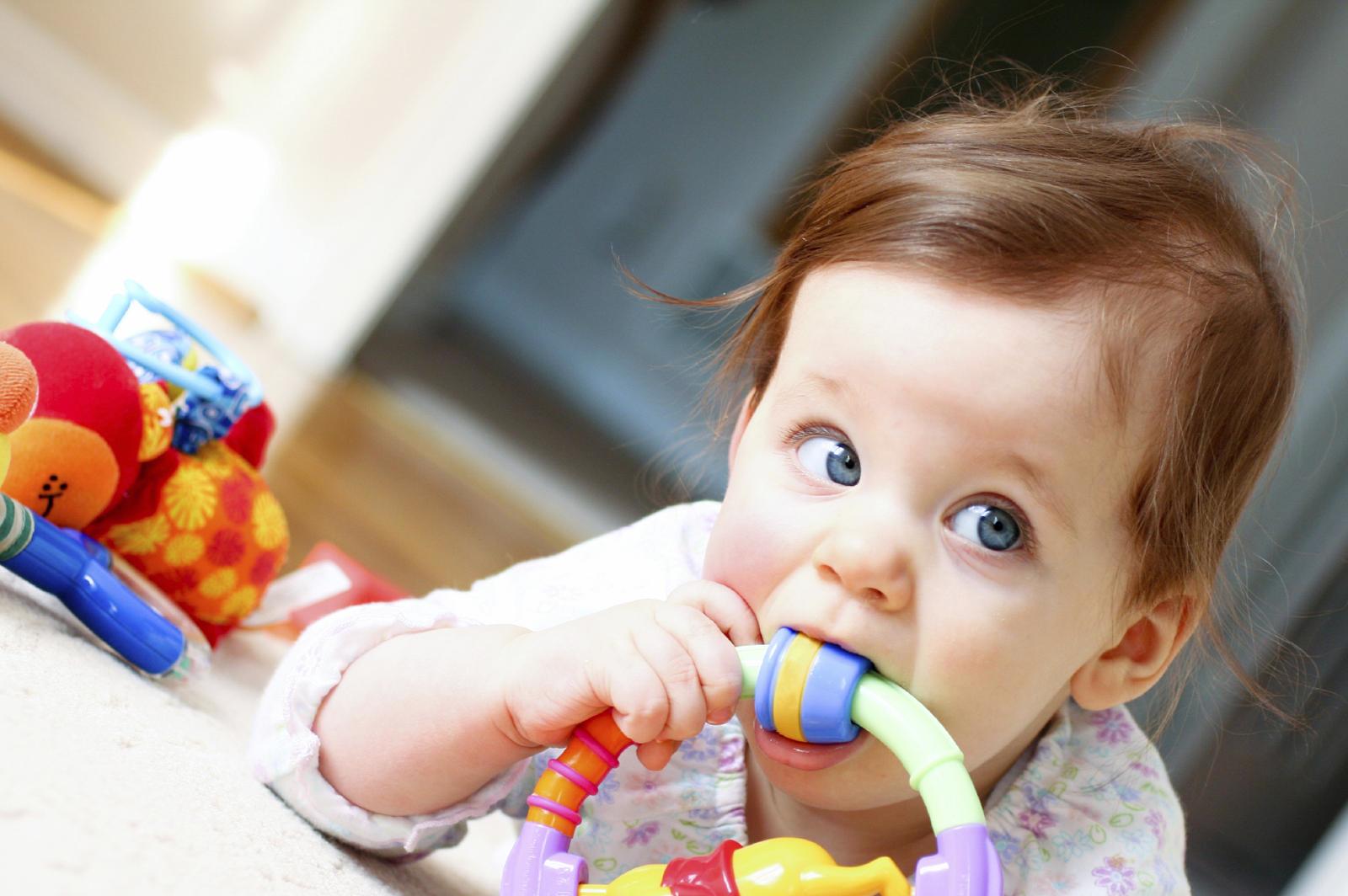 bébé avec un jouet dans la bouche