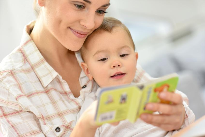 Assistante maternelle qui lit un livre à un bébé