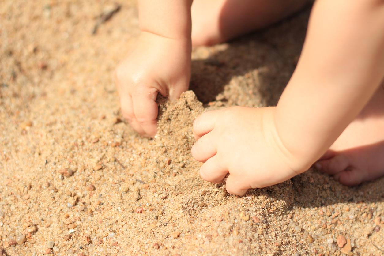 mains bébé dans le sable