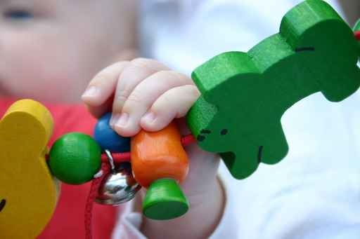 bébé qui touche un jouet avec ses mains