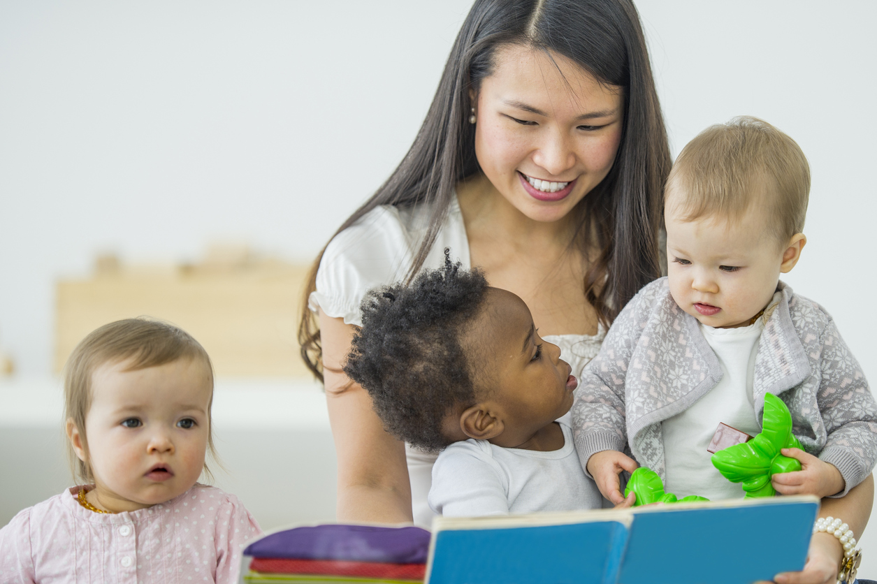 professionnelle lit un  livre à des jeunes enfants