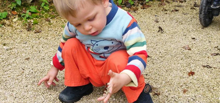garçon joue avec graviers