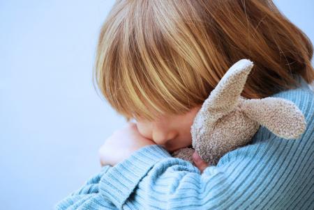 enfant tiste avec son doudou