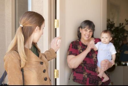 assistante maternelle avec bébé dans les bras  dit au revoir à une maman