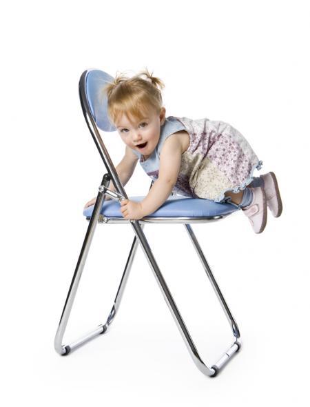 petite fille grimpe sur une chaise