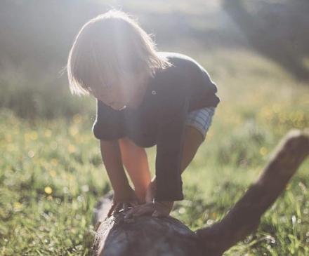 Enfant sur rondin