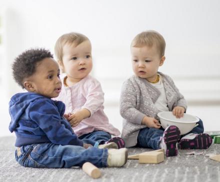 Trois bébés jouent ensemble