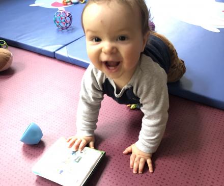 petit garçon joue sur un tapis en crèche