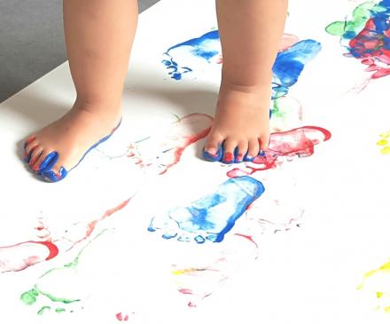 jeune enfant en activité peinture au pied