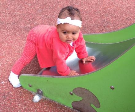 petite fille au pied d'un toboggan