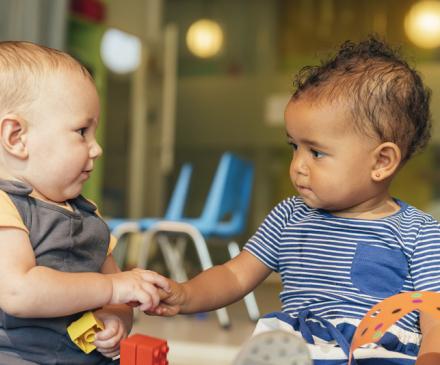 Bébés se tenant la main dans une crèche