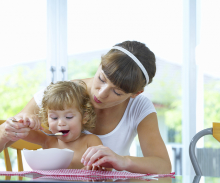 petite fille mange avec adulte