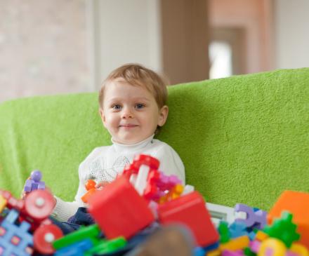 Un enfant est assis face à une pile de jouets