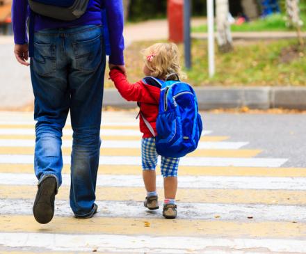 homme emméne enfant à l'école