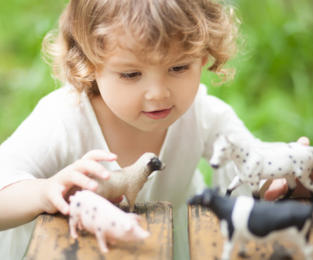 petite fille jouant avec figurines animaux de la ferme