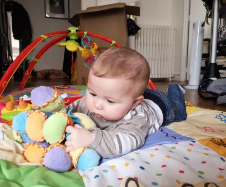 bébé à plat ventre joue