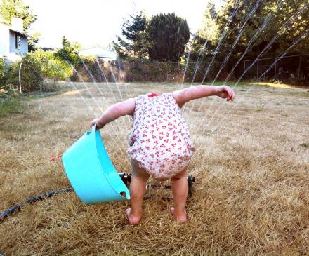petite fille joue avec l'eau