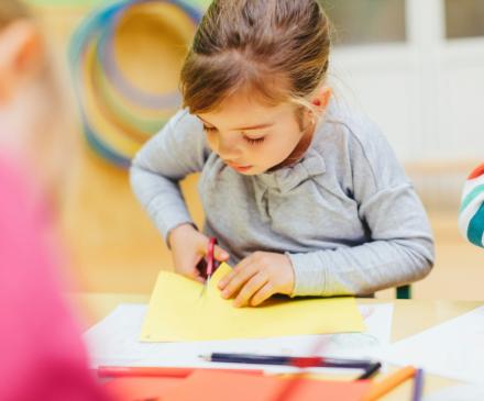 petite fille découpe à l'école maternelle
