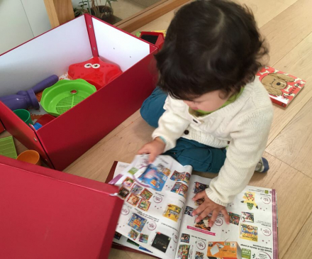 Petite fille avec un catalogue de jouets