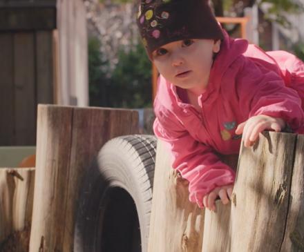 petite fille qui escalade des rondins