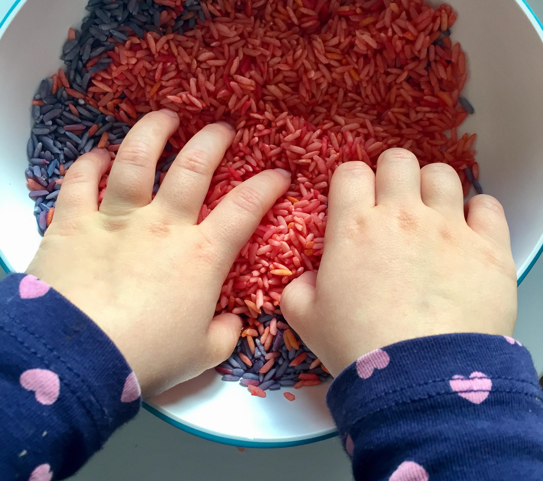 Bébé met ses mains dans du riz coloré
