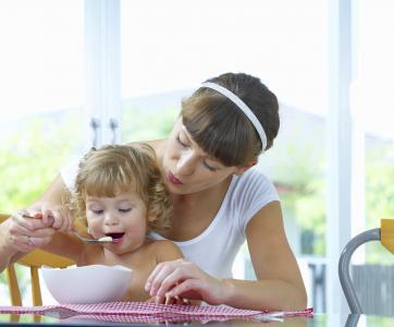 femme qui donne à manger à un enfant