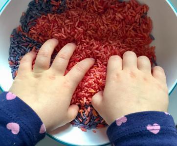 Mains de bébé dans du riz coloré