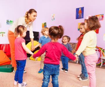 Des enfants font la ronde avec leur atsem à l'école maternelle
