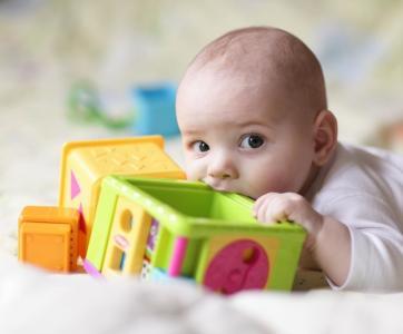 bébé mord un jouet à la crèche