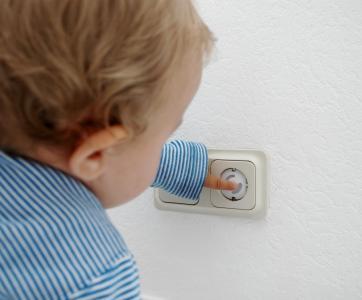 enfant met son doigt dans la prise