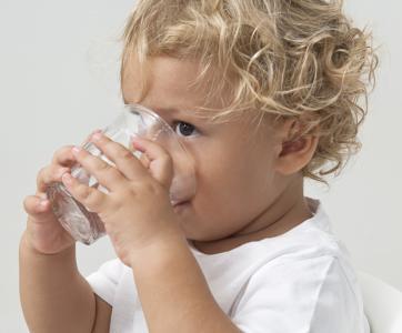 petit garçon qui boit dans un verre