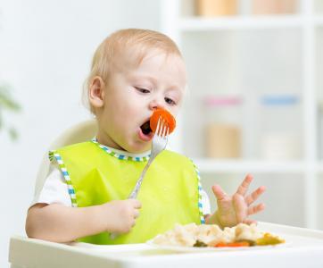 enfant qui prend son repas sur sa chaise haute